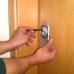 Imagen de un cerrajero abriendo una puerta con ganzúas.